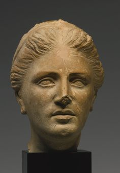 AN ETRUSCAN TERRACOTTA PORTRAIT HEAD OF A WOMAN, CIRCA 3RD/2ND CENTURY B.C. her finely modeled face with dimpled chin, outlined slightly parted lips, straight nose, and pierced ears, her hair parted in the center and brushed back from the temples, and bound in a fillet wound twice around the head.  Height 8 1/2 in. 21.6 cm.