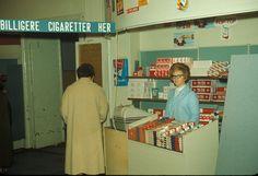 Butikkinteriør. Kvinnelig butikkansatt bak disk. Reklame for tobakk og vareplassering av tobakk i butikk Desk, Furniture, Vintage, Home Decor, Desktop, Decoration Home, Room Decor, Table Desk, Home Furnishings