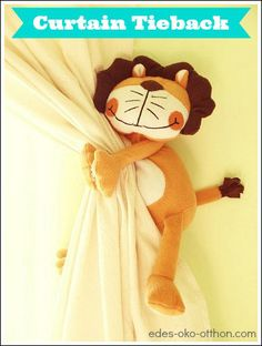 Sew a plastic ring onto back of stuffed animal, attach to hook on wall, and use as a curtain tieback