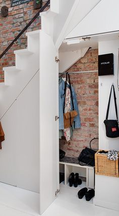 Contemporary entryway with white open staircase against an exposed red brick wall with white hardwood floors and under stairs mud room closet with coat rail and storage bench. Staircase Storage, Stair Storage, Closet Storage, Closet Under Stairs, Under Stairs Cupboard, Foyers, Under Staircase Ideas, White Hardwood Floors, Hallway Walls