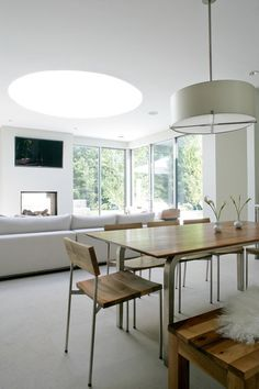 Here is a similar situation: Full-height windows at the corner are balanced by a large skylight. Note how the skylight also serves to give the large, open plan a focus over the seating area.