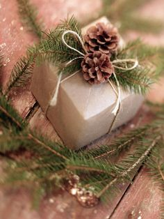 Pine cones and fresh greenery make great details on Christmas presents wrapped in simple brown craft paper and string bows.