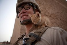 U.S. Marine Corps Lance Cpl. Kowshon Ye, a combat videographer with 1st Battalion, 5th Marines, Regimental Combat Team 8, plays with a kitten after conducting a raid in the village of Sareagar in Sangin, Afghanistan Aug. 13, 2011.