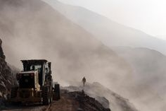 Heavy machinery is used in the clearing of debris on the road leading to the town of Camarones, in Arica, Thursday Apr. 3, 2014. The road was cut off due to the magnitude-8.2 quake that struck Chile's Northern coast on Tuesday. Authorities discovered surprisingly light damage from the quake.  Schools were closed, and large supermarkets and gas stations coordinated their reopenings Thursday with police and military to avoid problems with long lines of customers.