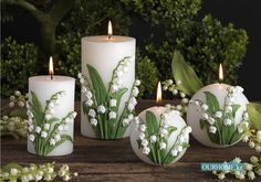 Candles decorated with Lily of the Valley flowers and leaves