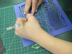 Students cut designs into 2 pieces colored paper then layer onto a third sheet of contrasting color.