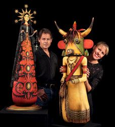 """Mark and Karen Klay pose with two of their gourd art pieces. The piece on the left, entitled """"Our Lady of Peace,"""""""
