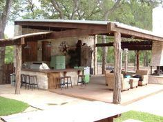 A rustic covered outdoor kitchen in Dallas goes big with a bar and metal pendants. Fun features include light green appliances and western-themed accessories in the outdoor living space designed by Evan Ratcliff with Key Residential.