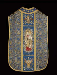 1909 St. Michael Chasuble. Blue and gold metallic brocaded ground, appliqued blue damask orphreys with embroidered and couched design in silk and metallic threads of crowned angel holding shield with instruments of the Passion, and St. Michael slaying thedragon on the front, stars and fleurs de lis around shoulders and neck, and two angels in roundels and Virgin in majesty on the back. Gold metallic braid trim. Deep pink lining.