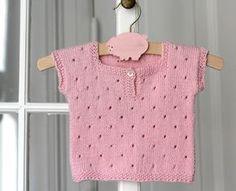 """Strikkefasthed 24 masker på pind nr.  3. En lille kortærmet T-shirt eller vest er suveræn som det lille """"ekstra"""" lag, når baby skal holdes varm på den lækre måde. Den lyserøde i hulstrik er strikket i bomuld/akryl og den gråmelerede i strukturmønster er i baby merinould – begge dele ultra bløde. Strikkeopskrift får du i 3 størrelser. Baby-T-shirt STR: 3/6-9/12-15/18 mdr. DET SKAL DU BRUGE: 2 ngl…"""