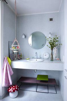 Salle de bain blanche et touches de couleurs subtiles / miroir rond White bathroom chez apolline à paris par julie ansiau.