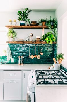 The bright green Moroccan tile backsplash is the star of this California kitchen, complemented by a bevy of houseplants shown off on rustic wooden shelving. | Photographer: Danae Horst | Designer: Justina Blakeney