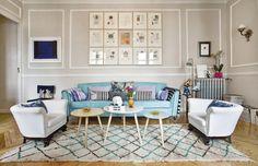 Un salón luminoso con sofá de ante turquesa y sillones blancos de estilo años 20.