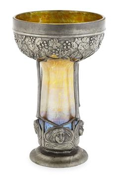 LOETZ, AUSTRIA  IRIDESCENT GLASS AND PEWTER MOUNTED VASE, CIRCA 1900,  the lemon yellow glass vase with peacock iridescence within a mount cast with a frieze of fruiting vines and to the base with maidens  20.5cm high