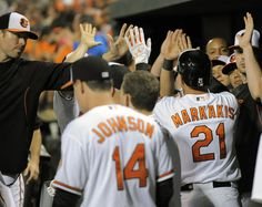 Orioles designated hitter Nick Markakis, right, receives congratulations in the dugout after scoring in the first inning against the Cincinnati Reds at Camden Yards.