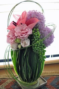 flower arrangement. Like the way leaves are used to cover the container.