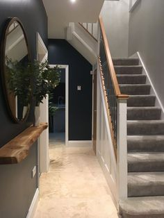 Dark blue and grey entrance hall, bronze round mirror with a floating oak shelf ... - Bea