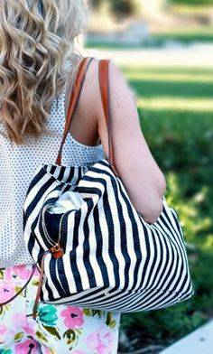 Oversized black & white striped tote bag with shoulder straps, top zipper closure and three inside sections