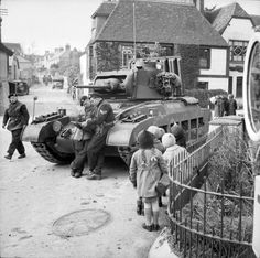 "English children watch the activity around a Matilda Mk II tank of British 44th Royal Tank Regiment during exercises against ""enemy"" parachute troops. Findon, Sussex, England, U.K. 4 March 1941."