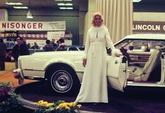 Image 11 of 14: Photo Courtesy: David Hutchinson Dressed in white full-length, fur-collared and cuffed awesomeness, this woman at the Lincoln display beckons showgoers to experience the good life inside a Lincoln Mark IV dressed in matching white inside and out, with bold red trim. In the background, the folks from Nisonger Instruments, still doing business in Mamaroneck, New York, were on hand to help British car enthusiasts with their Smiths gauges and accessories.