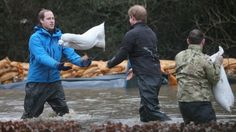 Princes William and Harry have joined troops trying to protect homes from storms sweeping southern Britain, helping to shift sandbags in Dat...