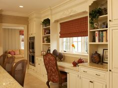 This traditional kitchen is designed to be the main gathering place of the home. The desk area is designed as part of the kitchen for the lady of the house. The chair fabric coordinates with the color of the custom window treatments.
