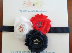 This festive handcrafted baby headband features three shabby roses in red, white, and navy with rhinestone star embellishments. Each rose