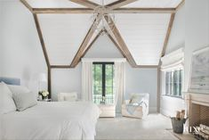 All-White Cathedral Ceiling Master Bedroom with Wooden Beams