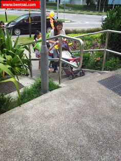 Mothers need to carry pram up stairs to access shopping mall    #Singapore.#CompasspointMallSingapore.  Difficulty in bringing the baby with the pram up the stairs into the #mall  #Sengkang is afamily oriented neighbourhoodwith lots of pregnant women and mothers pushing babies in prams.  The path to enter the shopping mall from the cluster ofHDB flats are surrounded by Cactus plantsleaving only a single staircase. For the alternate entry point you can only take an escalator up the overhead…