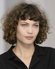 """The key to this naturally diffused look is the bangs, says Carey. """"Blow-dry your bangs with your fingers to loosen the curl, and leave the rest of the hair natural with tight curls."""" Finish with a flexible spray to keep the curls intact. Imaxtree - ELLE.com"""