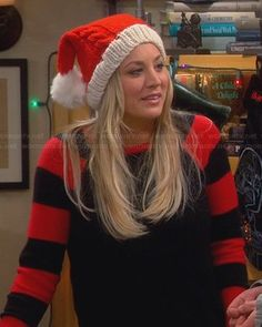 Penny's black sweater with red striped sleeves and knitted Santa hat on The Big Bang Theory. Outfit Details: https://wornontv.net/24189/ #TheBigBangTheory