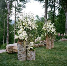 Backyard wedding altar - pretty floral arrangements on cut logs. Photo: A Bryan Photo / Event Planning & Design: Mariee Ami / Event Design, Floral Design: Wildflower Designs: