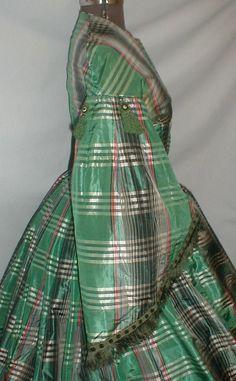 An elegant 1860's Civil War era green plaid silk dress. The fabric has a green, black, white and red plaid design.