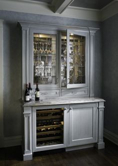 A standalone cabinet in white stained, carved wood holds glassware behind patterned glass upper cupboards over a marble countertop space. Lower half houses a full built-in wine cooler.
