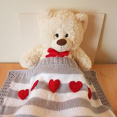 Knitted baby blanket, in a grey and white stripes, with a row of little red hearts The hearts are stitched on along the one border. The lacy border is crochet. This would match almost any baby theme for a nursery, and is perfect as a gift if you dont know the baby gender. Ideal