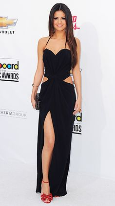 Selena Gomez at the Billboard Music Awards in a Dolce & Gabbana dress with cut outs. She accessorized with red bow front sandals by Giuseppe Zanotti, jewelry by Neil Lane, and a Judith Leiber clutch.