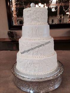 Swirled buttercream wedding cake with 'M' monogram.