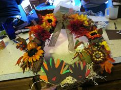 Thanksgiving wreath. Kids hands as turkeys and other stuff wired and or glued in. Simple to make. Just get a bunch of fall leaves and fall color flowers. And a few picks. Assemble and wore and hot glue and done. I used raffia as the nest under turkeys. I'm going to add eyes I just couldn't find mine.