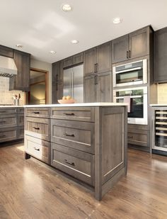 alder gray stained cabinetry, soft white quartz countertops and hand glazed backsplash tile. High quality details in the center island, premium built-in European appliances, and LED under cabinet lighting. Construction & Design by Steven Ray Construction, Inc.