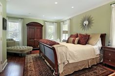 A beautiful bedroom that packs a lot of style into a small space!  The sleigh style bed pins down a gorgeous traditional area rug. Complementary colours in sage, olive, beige, gold, and burgundy dance around the room tying everything together.  An interesting piece of wall art shines over the bed, while natural light trickles in through the veils of drapery and mini blinds.