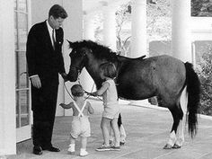 President John F. Kennedy spends some time at the White House with his children, Caroline and John Jr., and their pony, Macaroni.