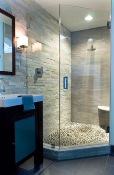 Frameless glass shower with black river rock floor and 3D stone wall. Found at www.pebbletileshop.com