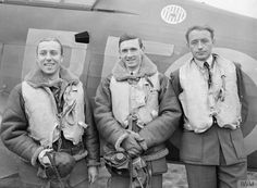 "F/L John A ""Johnny"" Kent is flanked by F/O Zdzisław K Henneberg (left) and F/O Marian Pisarek of No 303 Squadron RAF at RAF Leconfield on 24 October 1940. At the time, all RAF command posts in Polish fighter squadrons were doubled, so when the former Canadian pilot was made A flight commander in July, destroying 4 enemy aircraft by October, he was joined in September by Henneberg who scored 8 victories during the Battle of Britain."