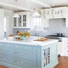 This lovely kitchen has a sky-blue island with a white marble top, several drawers and shelves for kitchen essentials.