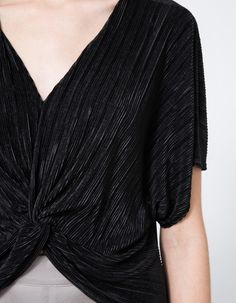 Modern cropped blouse from Stelen in Black. V-neckline. Kimono sleeves. Twist detail at front. High-low hem.   •Poly sateen •100% polyester •Hand wash cold, hang dry •Made in USA