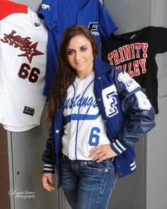 Senior softball player poses in the locker room with her jerseys for her senior portrait