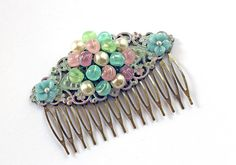 Filigree hair comb with patinaed Shabby Chic personality, is comprised of a fabulous 'Mad Men' era earring, and vintage glass flowers. The gorgeous pastel hues of pink, blue, green, and mauve blend beautifully with the softly colored filigree background. Swarovski crystal cabochons add glowing accents to the delicate flowers.