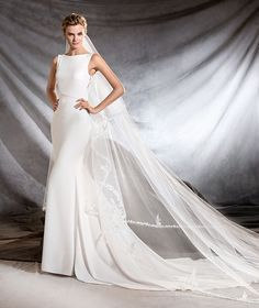 Pronovias Spring 2017 OLIANA - Mermaid wedding dress with a bateau neckline Sensual mermaid wedding dress with a bateau neckline. A magnificent creation in crepe with thread embroidery and gemstone details. A U-shaped opening at the back with elaborate embroidery and a line of feminine buttons gliding over the bride's silhouette.