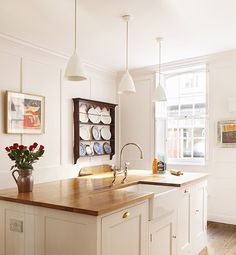 Beautiful wood countertop and simple bare windows.  And the details...the pewter pitcher and plate rack filled with blue and white dishes.  I love it all! ( I would only add brass pendant lighting.)