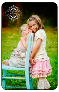 Beautiful little sisters in turquoise chair, pastel clothes, girly, sweet, summer sun, open country field
